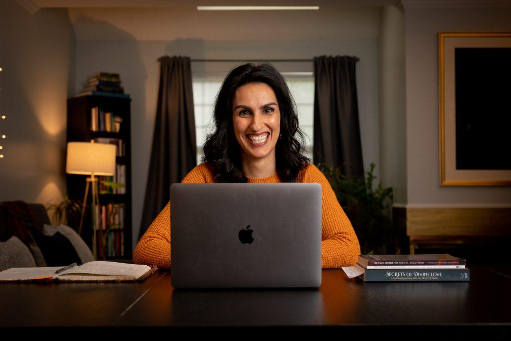 Sameera smiliing in front of her computer in yellow sweater